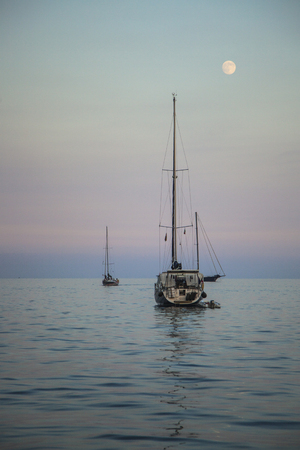 Anchored yacht in a quiet evening with a moonshine photo