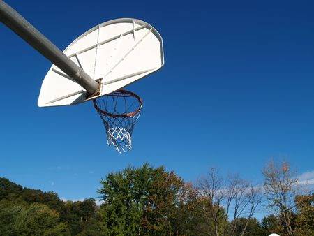 A basketball hoop extending out into a bright blue sky Stock Photo
