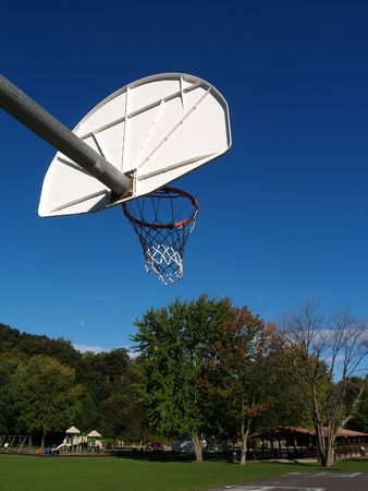 A basketball hoop extending out into a bright blue sky at the park Stock Photo
