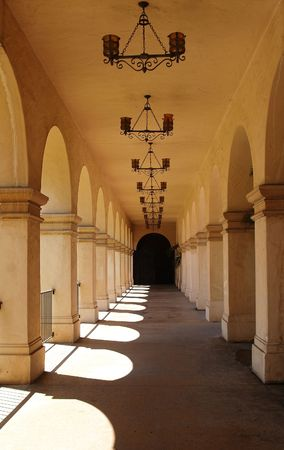 An outdoor breezeway lined with arches leading to beautiful gardens in Southern California.  Done with a heavy spanish influence Stock Photo