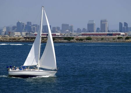 A sailboat speeds along in San Diego Harbor, California