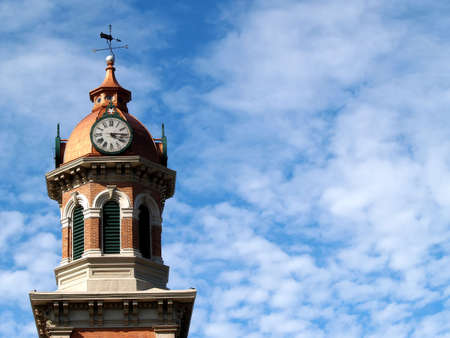 A brick and brass clock tower against a cloudy blue sky
