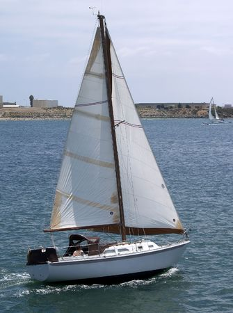 A small sail boat speeds along in San Diego Harbor on an overcast day