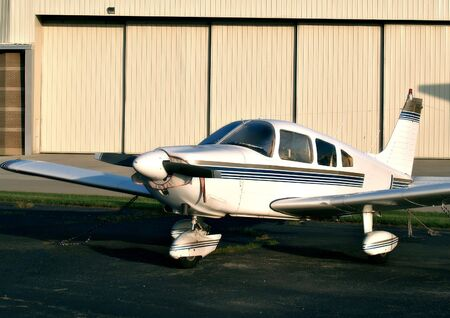 Single prop airplane sits in a tie-down area on the airfield in front of a large hangar