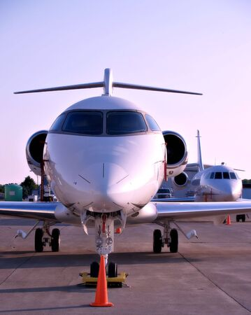 medium: Medium sized jet planes sit on the tarmac at a small airport