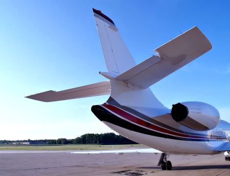 Tail view of a medium sized business jet sitting on the tarmac of a small airport