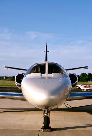 A small business jet waits on the tarmac for its passengers Фото со стока