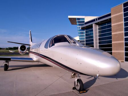 A small business jet waits on the tarmac for its passengers Stock Photo