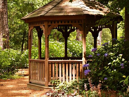 Wooden gazebo in the dappled sunshine of the garden