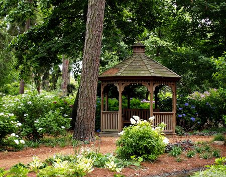 Small garden gazebo hidden by the flowers and trees
