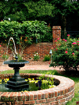 A water fountain sits in the middle of a pretty landscaped garden