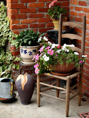 Summer still life of a wicker chair, pots of flowers, watering can, and a vase against a brick wall