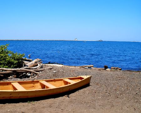 A small wooden rowboat sits on the shore of Lake Erie