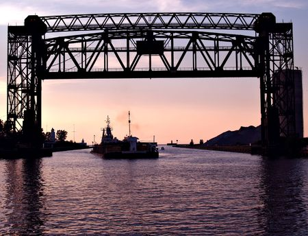 Trestle bridge raised over the Cuyahoga River in Cleveland, Ohio at dusk to allow a large cargo ship entrance to the harbor Stock Photo