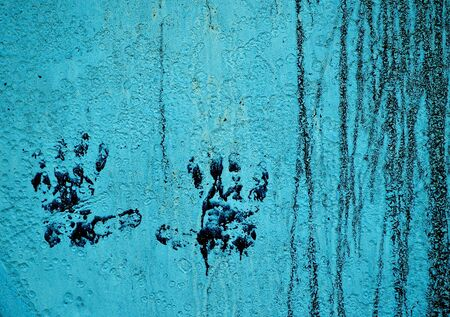 Set of dirty, grungy handprints on an old, cracked, streaked wall