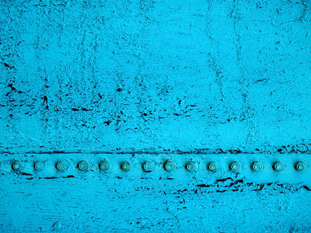 Close-up of old, cracked, dirty teal paint with the black base showing through and a line of bolts running across the surface