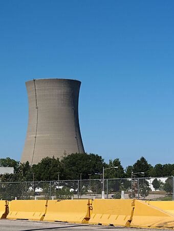 Twin nuclear power stacks rise above an office building into a clear blue sky