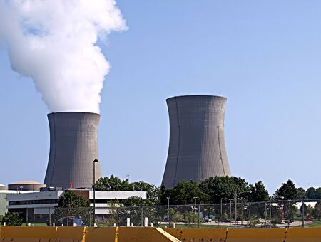 Twin nuclear power stacks rise into a light blue sky, smoke rising from one stack