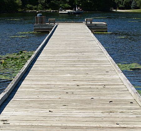 Long wooden planked dock stretching out into a deep blue lake in Ohio