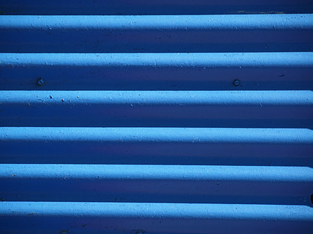 Blue corrugated metal with two screws suitable for a background
