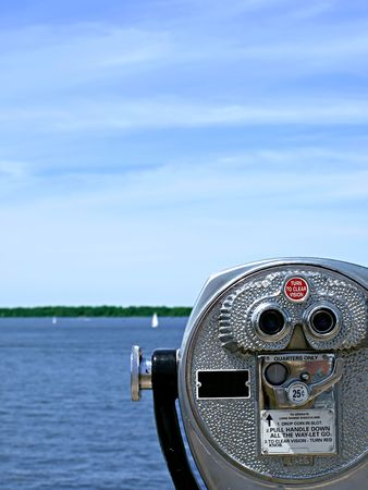 Pay-per-view binoculars look out over a pretty lake with sailboats in the far distance Stock Photo
