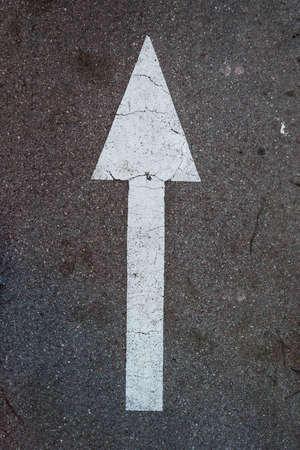 Withe and long arrow on the asphalt photo