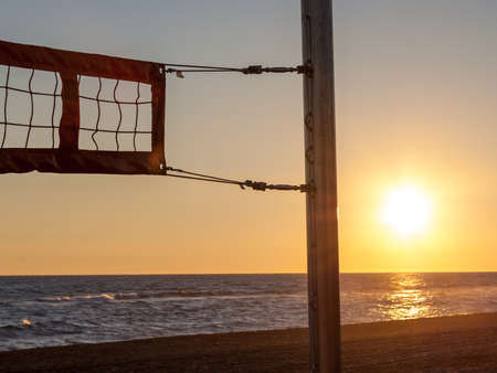 Volleyball net on the beach with the sunset Stock Photo