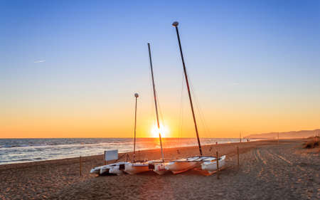 Boats on the beach in sunset and blue sky