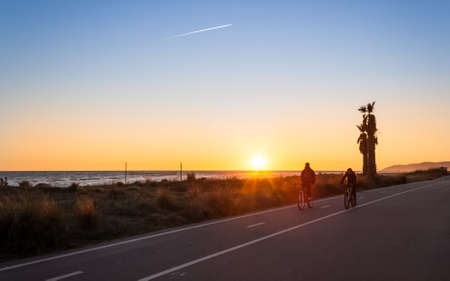 A couple of mountain bikers in sunset next to the beach