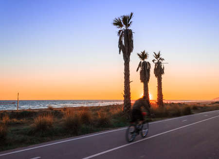One person ride on bike nest to the beac and sunset