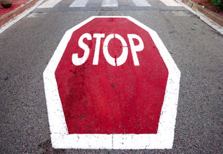 Red and big stop signal on grey asphalt