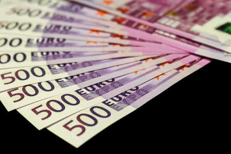 Lot of 500 euro bills isolated on black