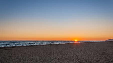 Beatiful orange sunset on the beach on calm and blue sky Stock Photo