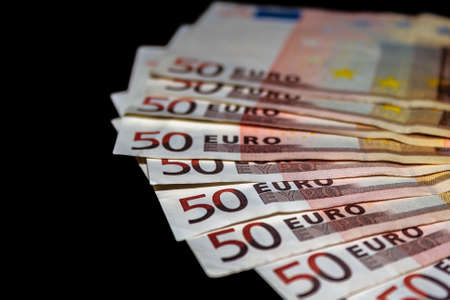 Lot of 50 euro bills isolated on black