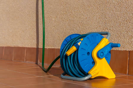 Green and blue gatering garden hose rolled