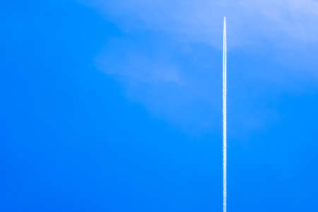 Airplane with contrail high in the blue sky