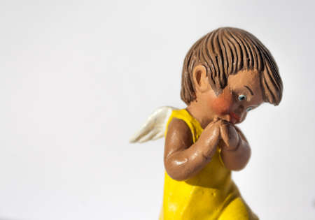 Cute angel figurine with yellow dress and white wings in a religious scene