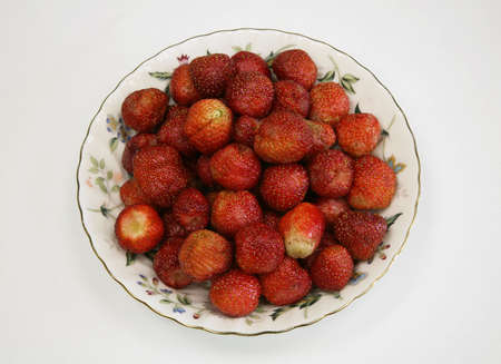 expects: The large ripe wild strawberry on a plate expects, when it will eat