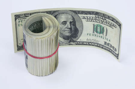 subsidize: Roll of banknotes by in 100 dollars tied up by an elastic band and one banknote by in 100 dollars