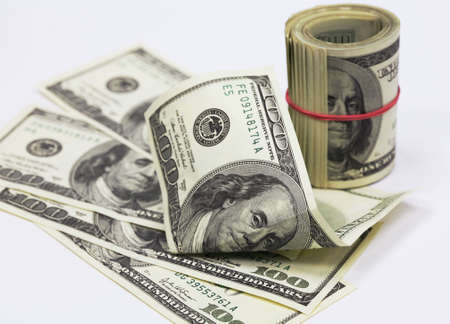 Roll of banknotes and separate banknotes in 100 US dollars photo