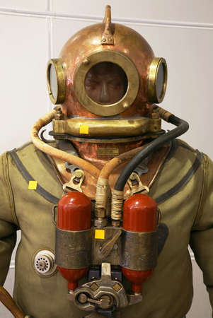 agachado: Visten al mannequin en un juego de salto con un casco de cobre redondo y los cilindros de ox�geno Foto de archivo