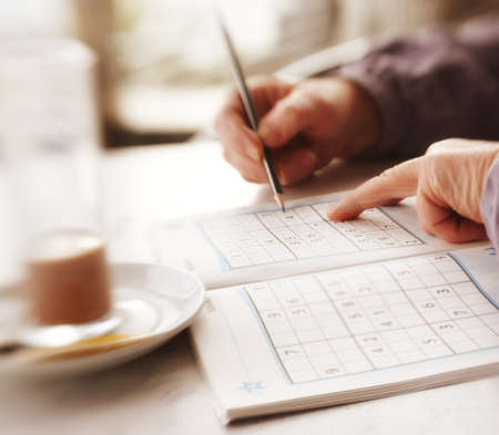 sudoku: Woman trying to solve Sudoku Puzzle - window, sunlight, and coffee  Stock Photo