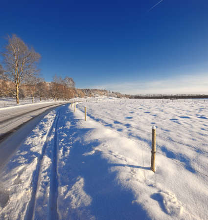 Winter landscape - countryroad, snow and blue sky photo