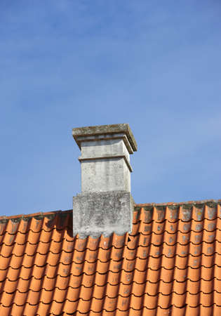 dilapidation: A sharp and detailed photo of the chimney of a family house