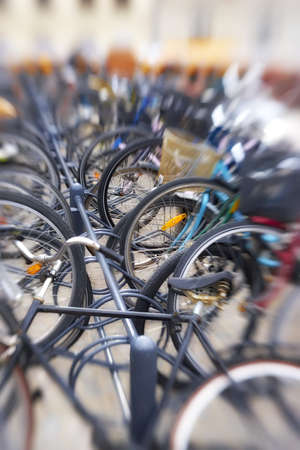 A lens blurred photo of lots of parked bikes. Symbolic content. photo