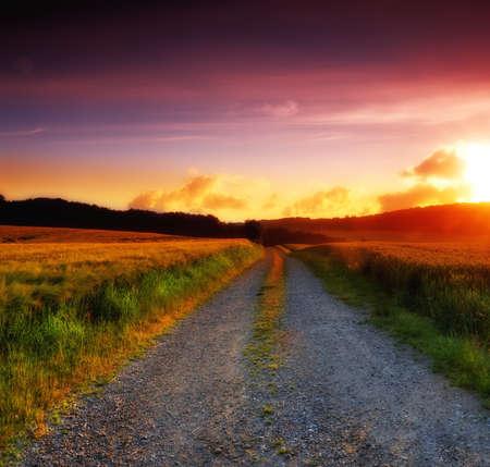 Straße und Landschaft während des Sonnenuntergangs
