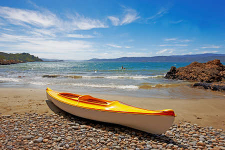 a photograph of a yellow kayak on the beach photo