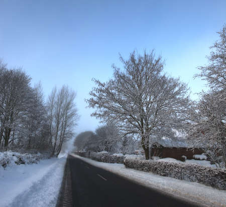 A winter photo of snowy countryside and road photo