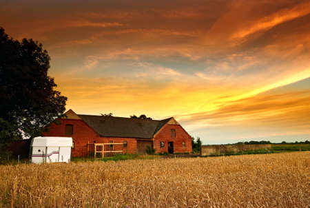 a photo of an old Danish farm in sunset