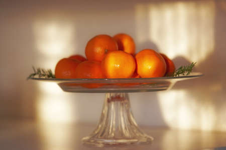 a photo of oranges on a glass plate at sunset photo